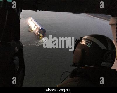 St Simons Island, Georgia, USA. 08 September, 2019. Aerial view from a U.S. Coast Guard rescue helicopter showing the M/V Golden Ray cargo ship as it rests inverted in the water after suffering a fire and capsizing in St Simons Sound Aerial September 8, 2019 off St Simons, Georgia, USA. The 656-foot-long vehicle carrier, listing heavily after suffering a fire with 24 crew members aboard.  Credit: U.S Coast Guard/Alamy Live News - Stock Photo