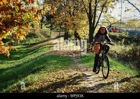 Teenage Girl Riding Bicycle On Field During Autumn - Stock Photo