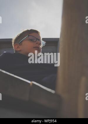 Low Angle View Of Boy Wearing Eyeglasses Sitting On Steps Against Sky - Stock Photo