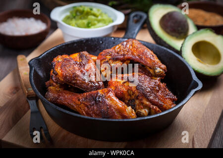 Grilled hot and spicy chicken wings with spices on dark background - Stock Photo