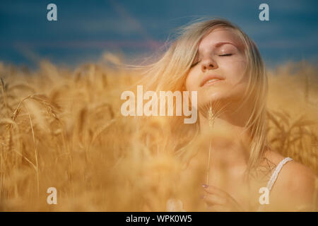 nature, summer holidays, vacation and people concept - face of happy smiling woman or teenage girl n in hat on cereal field - Stock Photo