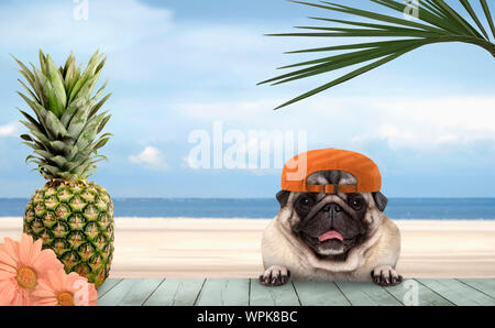 smiling tropical summer pug dog with orange cap, with paws on vintage green wooden table and sea and beach on background - Stock Photo