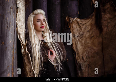 Outdoors portrait of beautiful furious scandinavian warrior ginger woman in a traditional clothes with fur collar, with sword in her hand and wooden V - Stock Photo
