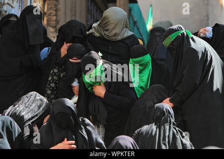 Khoramabad, Iran. 22nd June, 2019. Chehel Minbari is a special tradition practiced in Khoramabad, in which thousands of women commemorate the martyrdom anniversary of Imam Hossein. The women cover their faces completely with black or green cloth, and walk in silence with candles. The Chehel Minbari tradition is upheld every year on Tasu'a, the 9th of Muharram, as a show of solidarity with the sister of Imam Hussein, Hazrat Zainab. The ritual starts after participants have said their dawn prayers and ends at dusk prayers. Credit: Mazyar Asadi/ZUMA Wire/Alamy Live News - Stock Photo