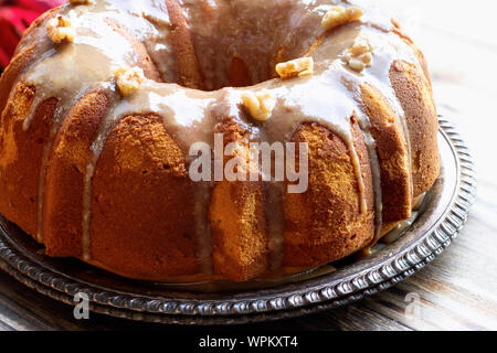 Delicious, Pumpkin Spice Bundt Cake frosted with brown sugar glaze and walnuts oven a rustic wood table background. - Stock Photo