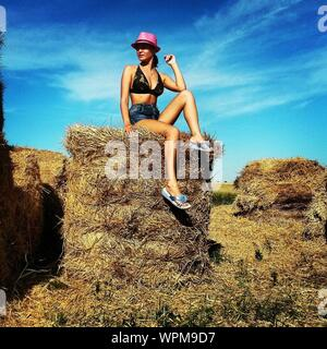 Woman Sitting On Hay Bale At Farm Against Sky - Stock Photo
