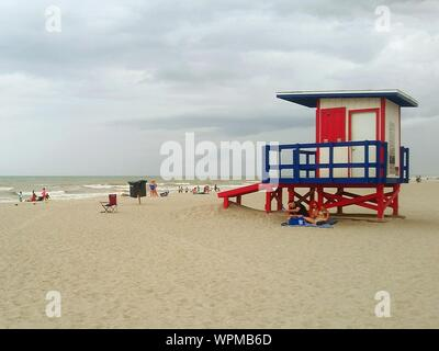 People By Lifeguard Hut On Sandy Beach - Stock Photo