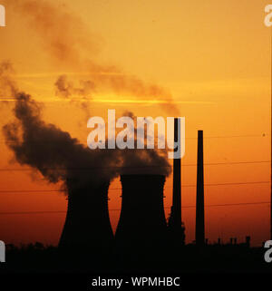 Smoke Emitting From Silhouette Cooling Towers At Industry Against Sky During Sunset - Stock Photo