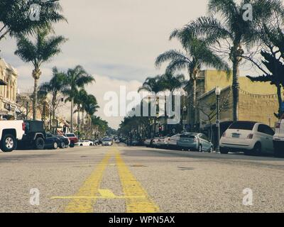 Cars Parked At Roadside In City Against Cloudy Sky - Stock Photo