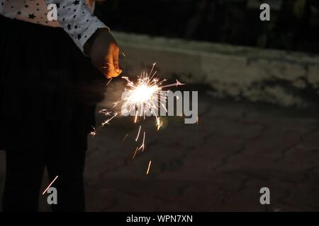 Close-up Of Hand Holding Diwali Cracker Against Blurred Background - Stock Photo