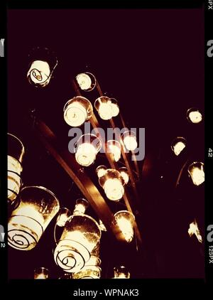 Low Angle View Of Pendant Lights Hanging From Metallic Rod - Stock Photo