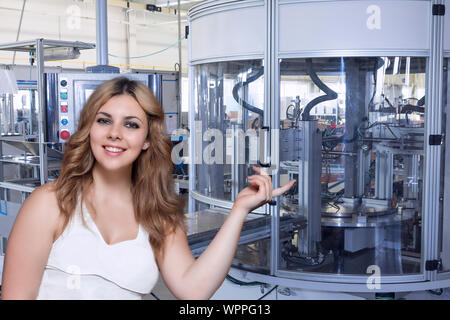 Smiling long haired young woman is showing automatic production line in the interior of an industrial plant. All potential trademarks are removed. - Stock Photo