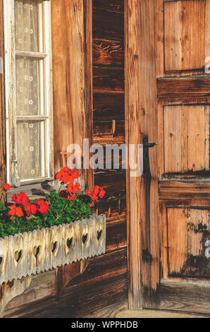 Wooden Alpine hut with typical red geranium flowers in the windows. Alpine chalet. Bavarian wooden huts. Flower decorations. Traditional flower, style. Bavaria, Austria, Switzerland. The Alps. - Stock Photo