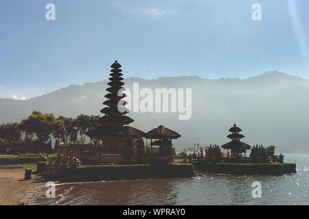 Pura Ulun Danu Bratan Temple By Lake Against Mountains And Sky On Sunny Day - Stock Photo