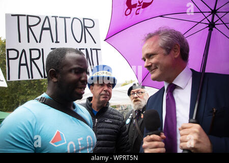 London, UK. 9th September, 2019. Richard Braine, the leader of Britain UKIP (UK Independence Party) pictured on College Green opposite the Houses of Commons with a purple umbrella and speaking to a member of the press, under the watchful eye of Steve Bray or Mr Stop Brexit. Credit: Joe Kuis / Alamy News - Stock Photo