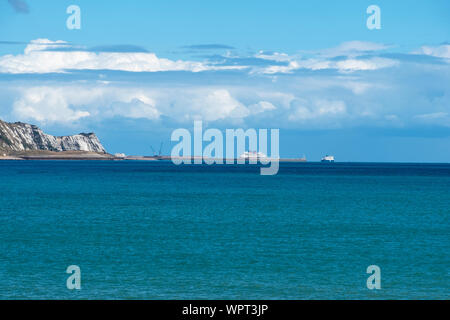 View from Folkestone Harbour across the bay to the distant port of Dover, Kent, UK - Stock Photo