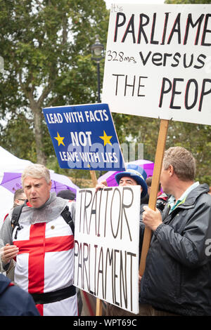 London, UK. 9th September, 2019. Pro-Brexit supporter dressed in the England flag and a large board 'traitor parliament' at a demonstration on College Green, opposite the Houses of Parliament, today. The well-known anti-Brexit activist Steve Bray with a blue hat and carrying a 'lead with facts and not leave with lies' placard is just visible behind the large white board with black writing. Credit: Joe Kuis / Alamy News - Stock Photo