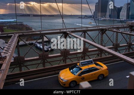 Yellow Cab Crossing the Brooklyn Bridge with sun rays over a distant Statue of Liberty, New York, USA - Stock Photo