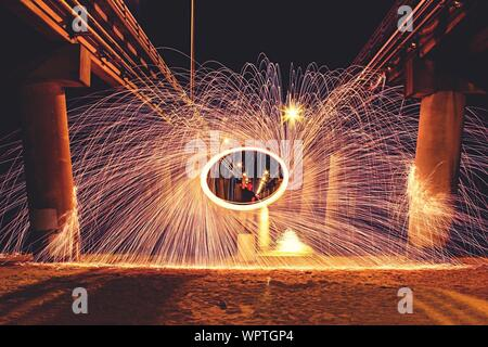 Man Spinning Wire Wool Below Bridge On Beach At Night - Stock Photo