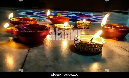 Close-up Of Lit Diyas By Rangoli - Stock Photo