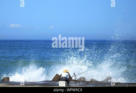 View Of Man Fishing And Waves Crashing On Rocks - Stock Photo