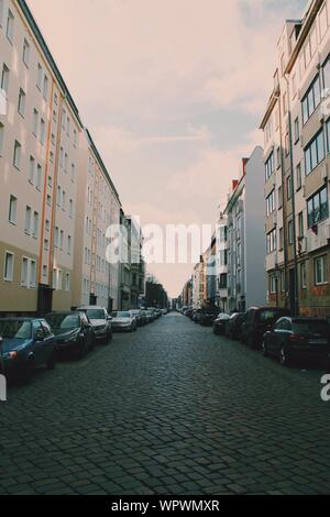 Cars Parked In Front Of Houses Against Cloudy Sky - Stock Photo
