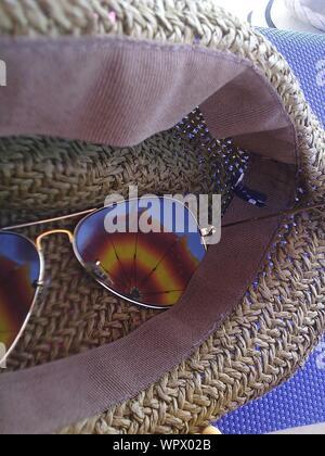 Reflection Of Umbrella In Sunglasses On Sun Hat - Stock Photo