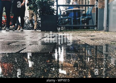 Puddle On Street With People Walking In Background - Stock Photo