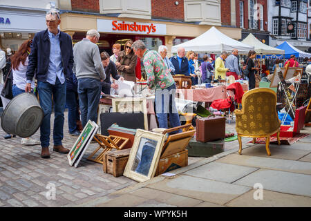 People browsing at a bric-a-brac stall at Guildford Antique & Brocante Street Market, High Street, Guildford, Surrey, southeast England, UK - Stock Photo