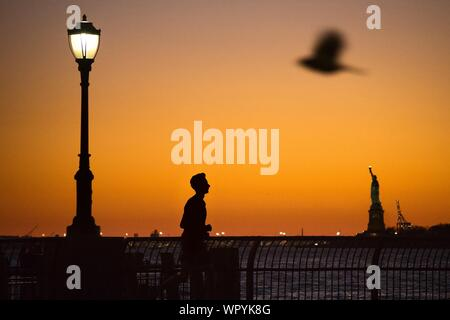 Side View Of Silhouette Man Jogging With Statue Of Liberty In Background During Sunset - Stock Photo