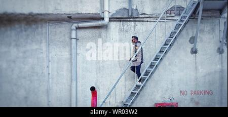 Full Length Of Man Walking On Staircase By Wall - Stock Photo