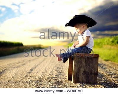 Side View Of Toddler Wearing Hat Sitting On Wooden Bench At Roadside Against Sky - Stock Photo