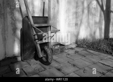 High Angle View Of Wheelbarrow Leaning On Wall In Back Yard - Stock Photo