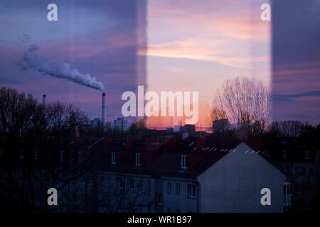 Smoke Stack Emitting Pollution Against Sky During Sunset Seen From Window - Stock Photo