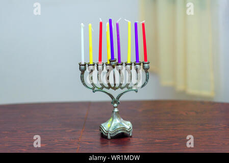 Jewish holiday Hanukkah background with menorah and colorful candles on wooden table in home. Cozy image menorah ready for lighting. - Stock Photo
