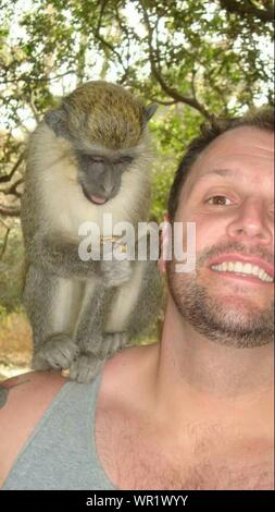 Portrait Of Smiling Man With Monkey On Shoulder At Zoo - Stock Photo