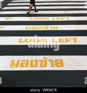 Low Section Of Woman Walking On Zebra Crossing Road Sign - Stock Photo