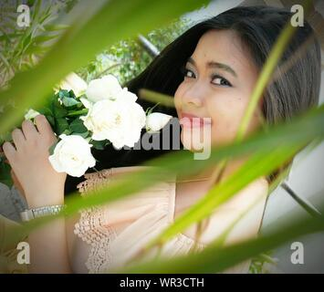 Portrait Of Smiling Young Woman Holding Flowers Seen Through Plants - Stock Photo