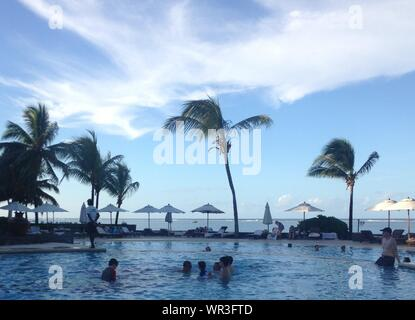People Enjoying In Swimming Pool Near Sea - Stock Photo
