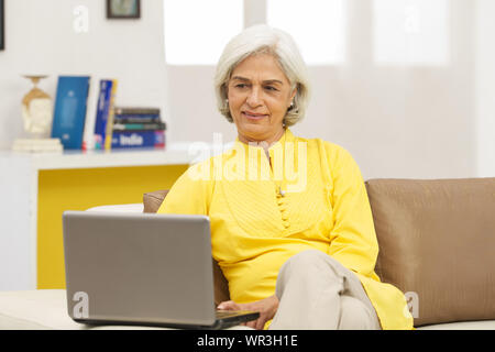 Senior woman sitting on couch in living room