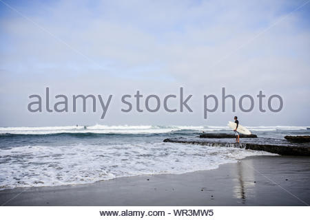 An older surfer standing on rocks, gazes out over the ocean near San Diego, California, USA - Stock Photo