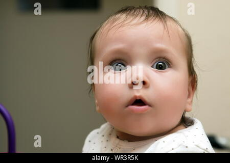 Close-up Of Surprised Baby Girl At Home - Stock Photo