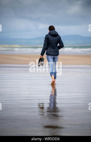 Woman carrying shoes walking barefoot on Benone Beach, Coleraine, Northern Ireland, UK. Walking away from camera