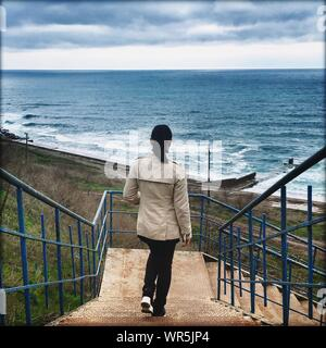 Full Length Rear View Of Woman Walking On Steps Leading Towards Sea Against Sky - Stock Photo