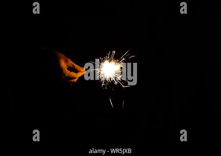 Close-up Of Hand Holding Diwali Cracker Over Black Background - Stock Photo