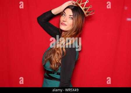 Portrait Of Young Beautiful Woman Wearing Crown Standing Against Red Background - Stock Photo