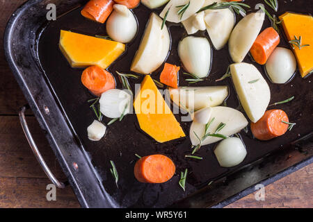 Vegetable bake - Uncooked vegetables in oven tray - top view photo of butternut, potato, onion, carrot and garlic pieses topped with fresh rosemary un - Stock Photo