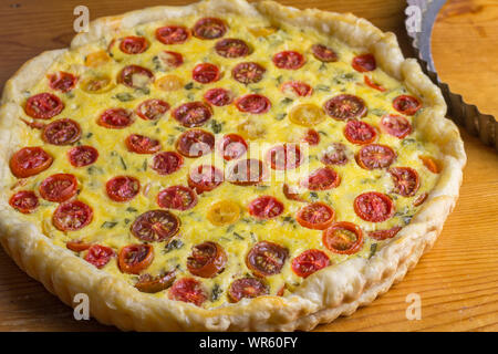 Cherry tomato tart horizontal image of puff pastry tomato cheese and egg quiche out of oven - Stock Photo