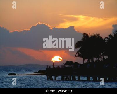 Pier Over Sea By Silhouette Coconut Palm Tree Against Sky During Sunset - Stock Photo