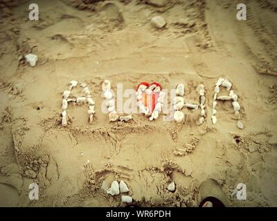 High Angle View Of Text Made From Pebbles On Sand - Stock Photo